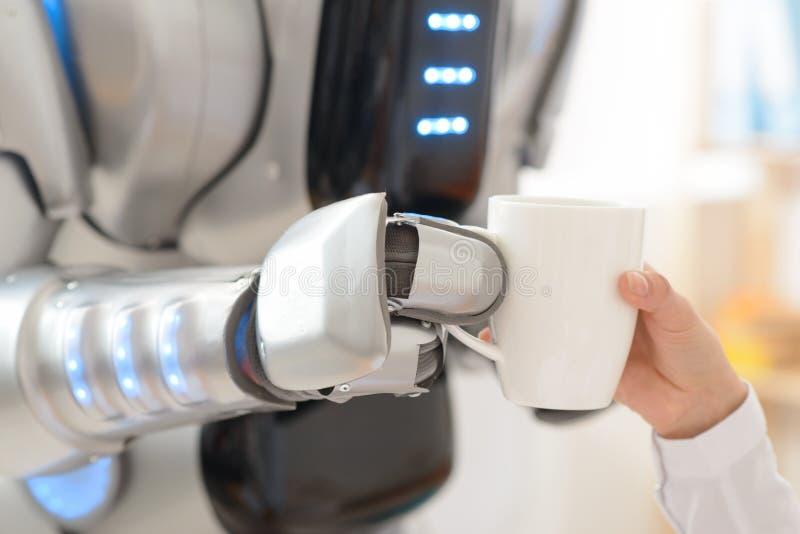 Robot piacevole che dà tazza di caffè ad una ragazza fotografia stock libera da diritti
