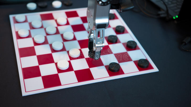 Robot playing checkers. Hand manipulator moves checkers. Robot playing checkers hand manipulator moves checkers stock photo