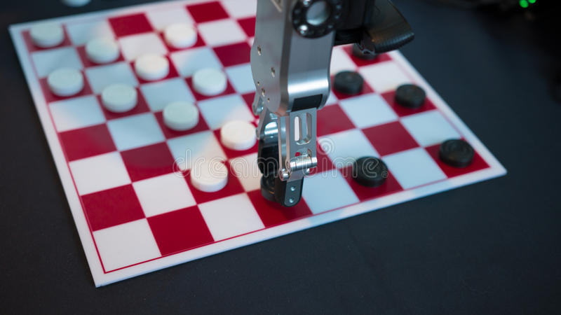 Robot playing checkers. Hand manipulator moves checkers. Robot playing checkers hand manipulator moves checkers stock photography