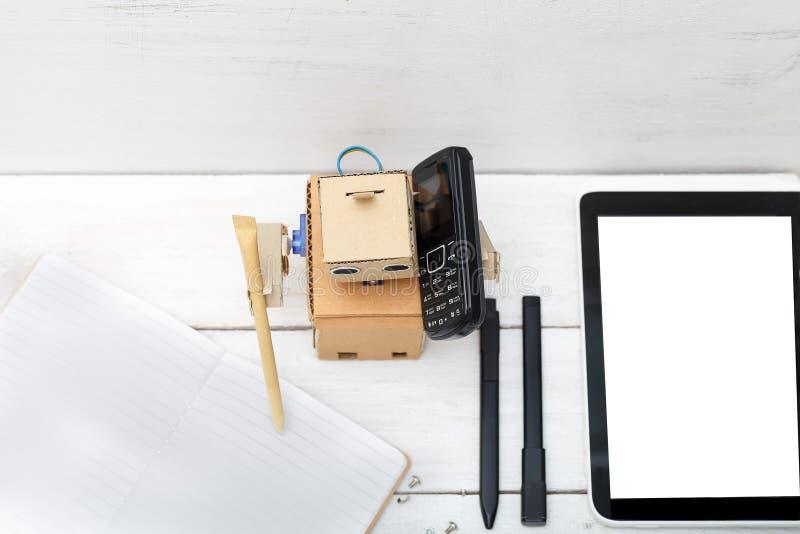 Robot pracy Pisze w dzienniczku i opowiadać na telefonie obrazy royalty free