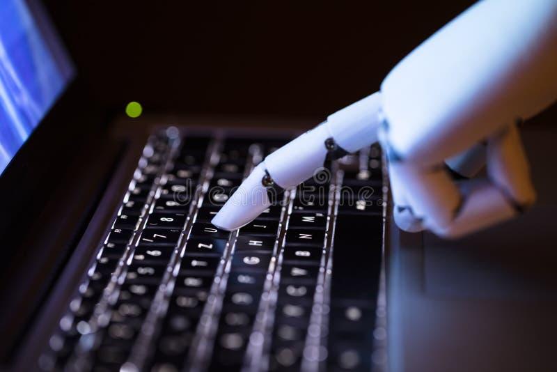 Robot que mecanografía en el ordenador portátil imagen de archivo libre de regalías