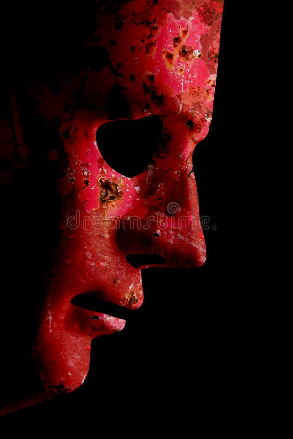 AI robotic face profile close up rusty red. Robot rusty decaying red face mask side view close up with textured skin and blank eyes. Black background and space royalty free stock photography