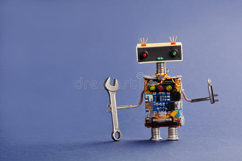 Robot serviceman with hand wrench and screwdriver on blue background. Abstract mechanical toy worker made of electronic royalty free stock images