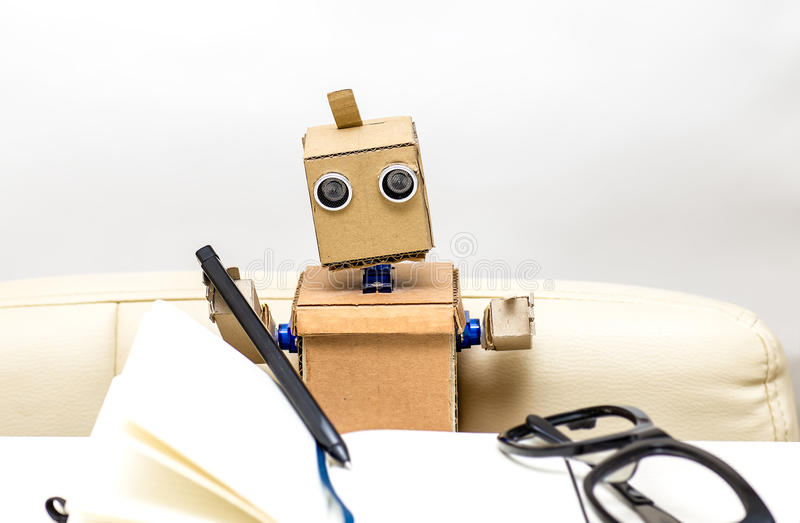 Robot is sitting on a chair at a desk light stock image