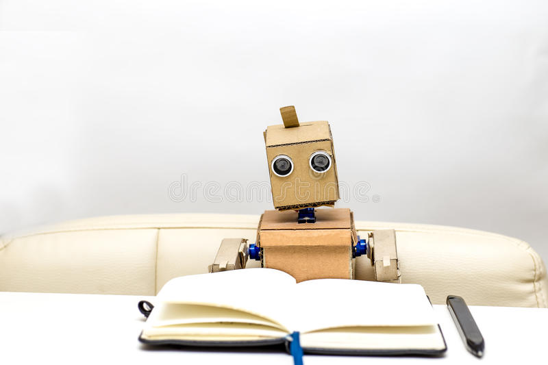 Robot is sitting at a table on a light background, stock photo