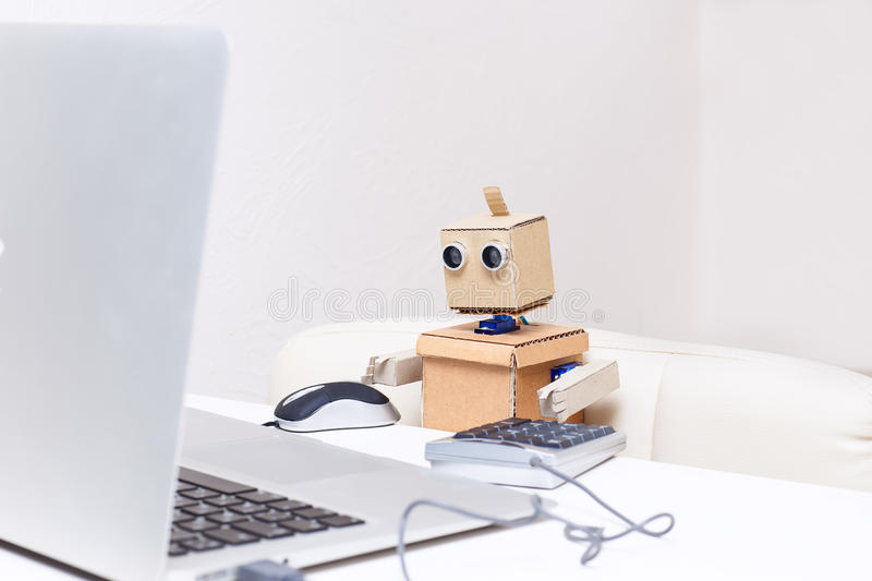 Robot is sitting at the table and working at a laptop royalty free stock photography