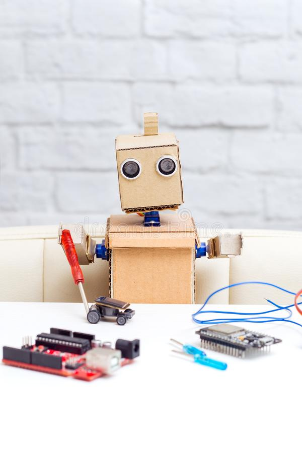 The robot is sitting at your desk and holding a screwdriver. Artificial intelligence royalty free stock photo