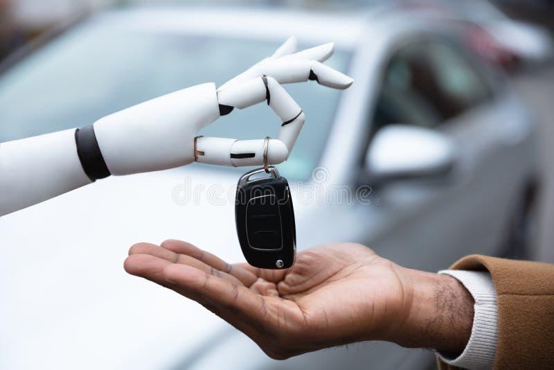 Robot som ger biltangent till mannen arkivfoto