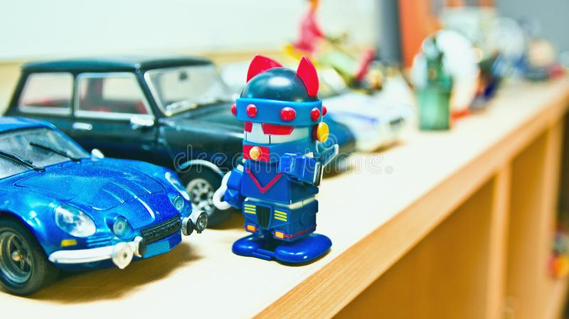 The robot is standing in front of his blue car. stock photo