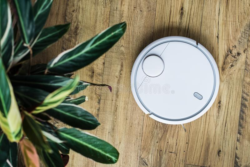 Robot stofzuiger op houten vloer De mening vanaf de bovenkant Slim huisconcept Het automatische schoonmaken stock afbeeldingen