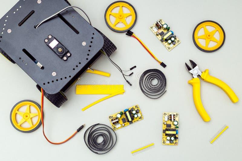 Robot sur des roues et des outils jaunes Configuration plate photographie stock