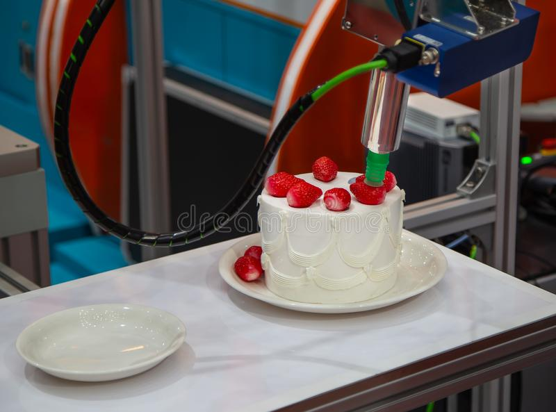 Robot topping strawberry on cake royalty free stock photos