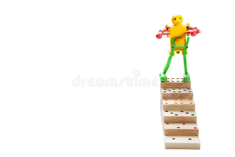 Robot toy standing on top steps of wooden domino, on white back. Ground, clipping path. copy space of your text royalty free stock images