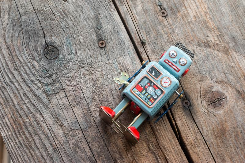 Robot toy, symbol for a chatbot or social bot and algorithms. Wood texture. Artificial intelligence ai data big computer future internet itics twitter elections royalty free stock image