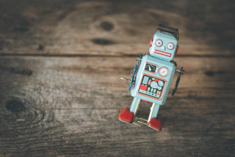 Robot toy, symbol for a chatbot or social bot and algorithms. Wood texture. Artificial intelligence ai data big computer future internet politics twitter stock images