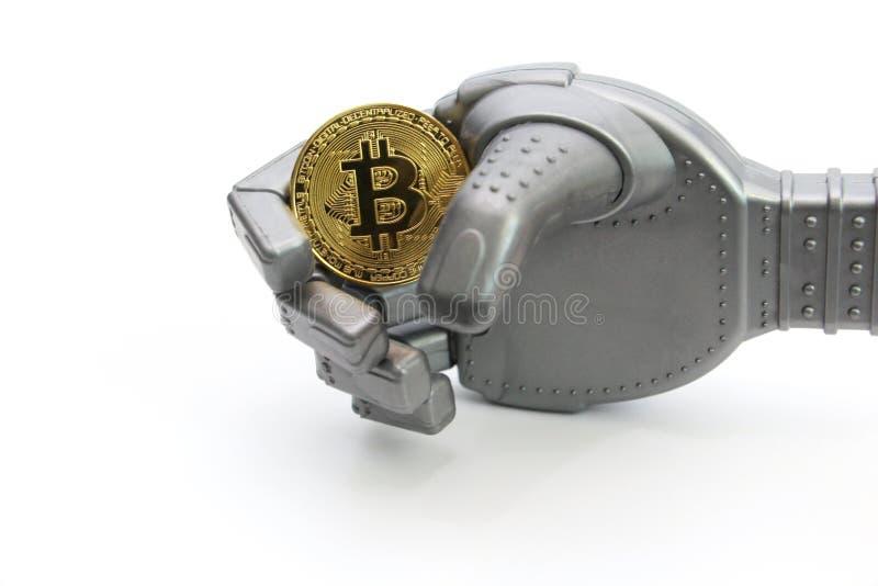 Robot trzyma jeden złocistą monetę - bitcoin Bia?y t?o zdjęcia stock