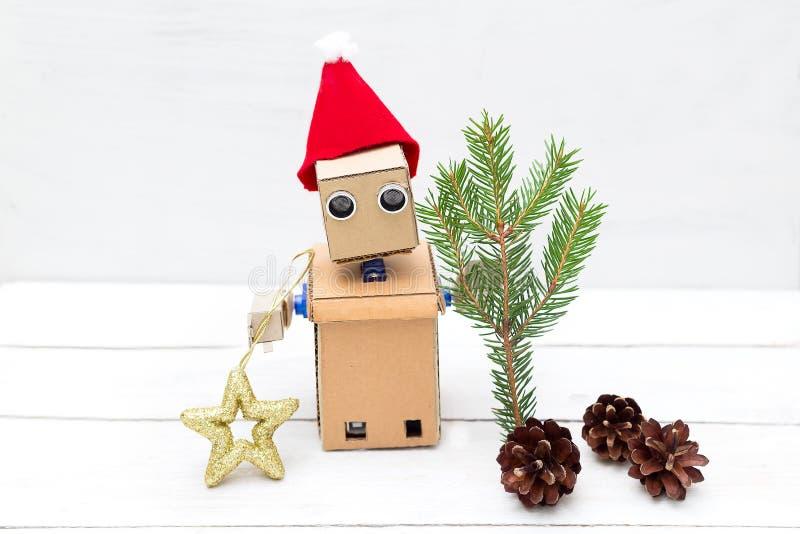 Robot trzyma sprig jodła i nowego roku ` s zabawkę w jego ręce zdjęcie stock