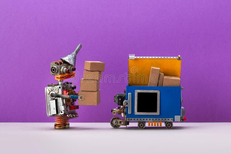 Robot uploads parcels into an autonomous delivery robotic courier truck. Automation service of transportation and. Shipment. purple background, copy space for royalty free stock image