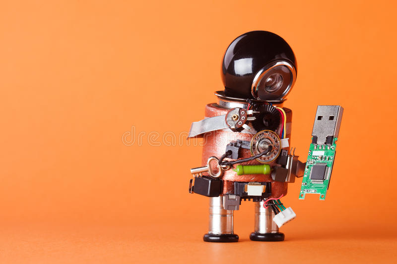 Robot with usb flash storage stick. Data storing and robotic technology concept, fun toy character black helmet head. Copy space,. Orange background, macro view royalty free stock images