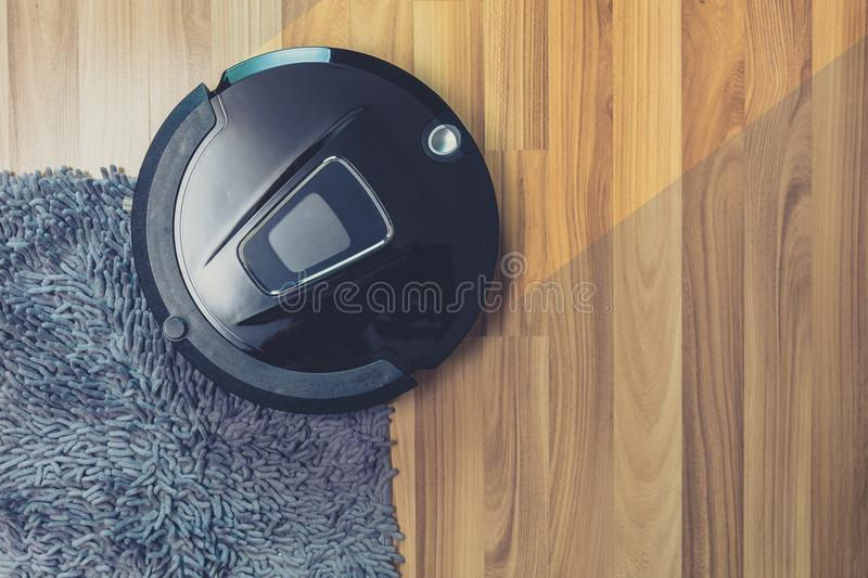 Robot vacuum cleaner cleaning on dusty wooden floor. And carpet royalty free stock photo