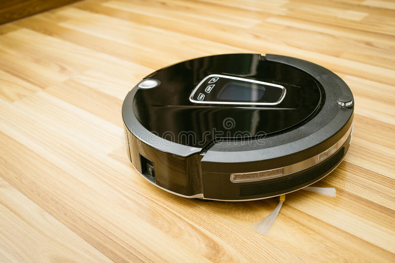 Robot vacuum cleaner on laminate wood floor. Smart robotic automate wireless cleaning technology machine in living room royalty free stock photos