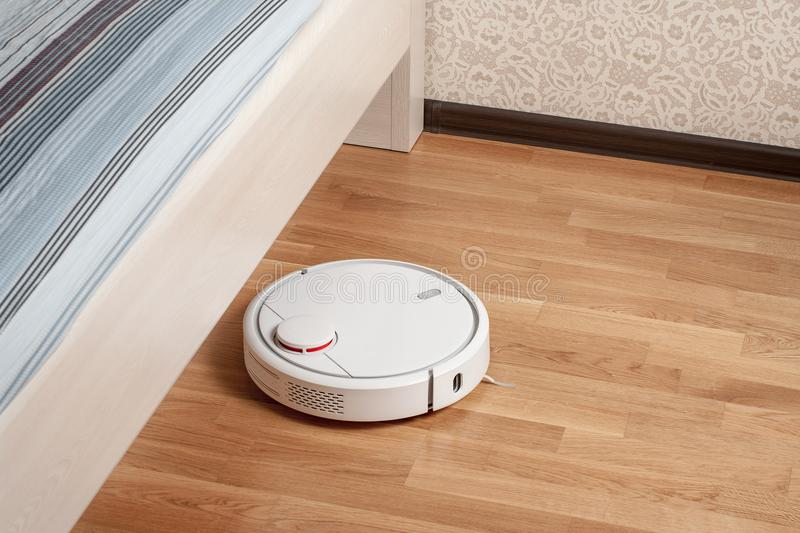 Robot vacuum cleaner runs on wood parquet floor under bed in bedroom. Modern smart cleaning technology housekeeping.  royalty free stock photography