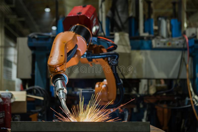 Robot is welding part in automotive factory. Industrial robot is welding assembly automotive part in car factory royalty free stock image