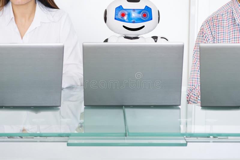 Robot z sztuczną inteligencją i istota ludzka jako koledzy przy pracą zdjęcie royalty free