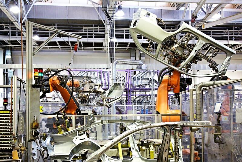 Robotachtige wapens in een autofabriek stock afbeeldingen