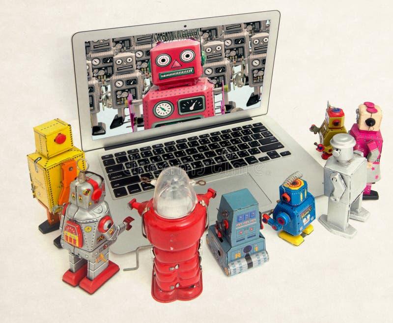 Robotar pratar till varandra i en bärbar dator royaltyfria foton