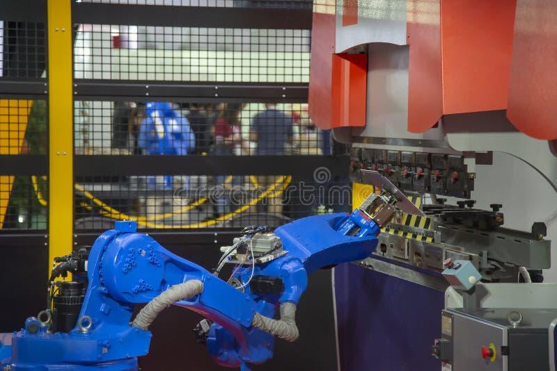 Robotarmen för att räcka arkmetall i böjande process royaltyfria foton