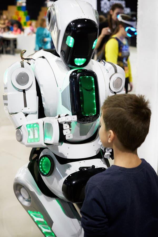 Roboter androider Cyborg verständigt sich mit einem kleinen Jungen stockfoto