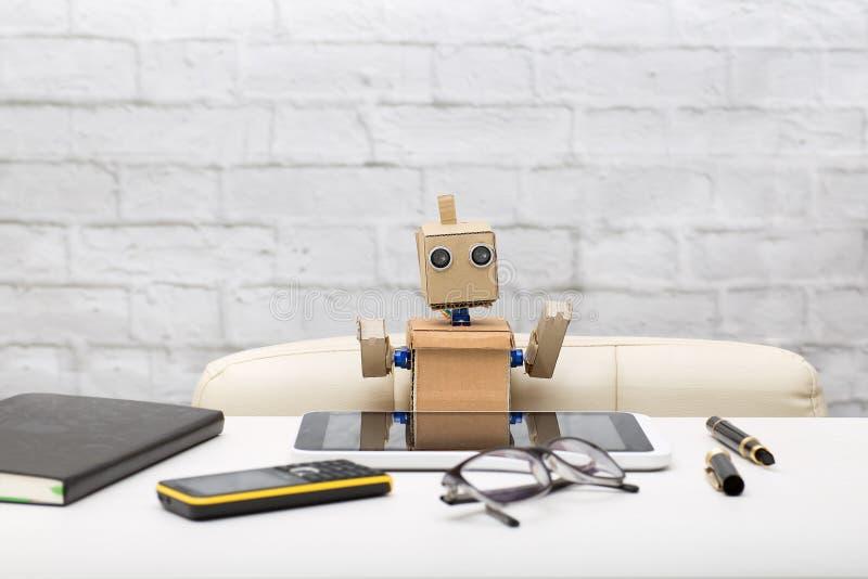 Roboter schreibt im Verlauf der Arbeit, Tagebuch, Stift, Tablette lizenzfreies stockfoto