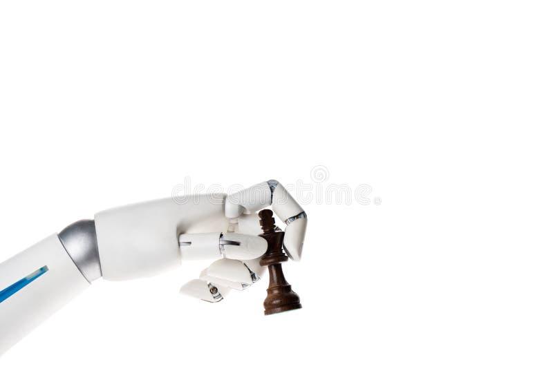 Roboterhand, die Schachkönigzahl lokalisiert auf Weiß hält lizenzfreie stockfotografie