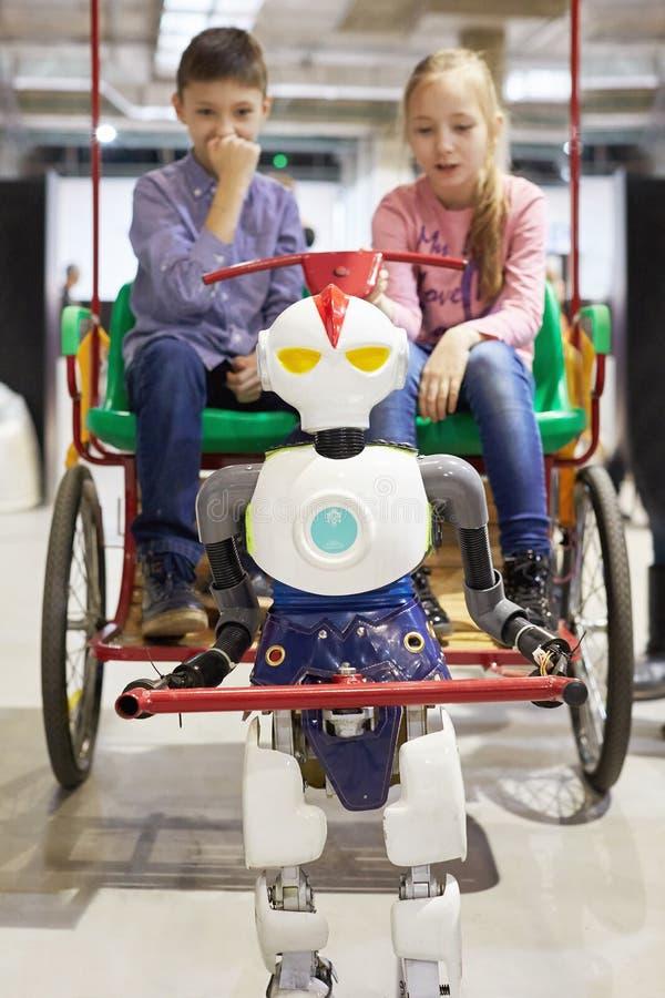 Roboterrikscha fährt Kinder in einem Warenkorb lizenzfreies stockbild