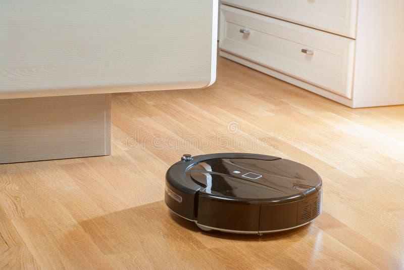 RoboterStaubsauger läuft unter Bett im Schlafzimmer in den Strahlen der Morgensonne stockbild