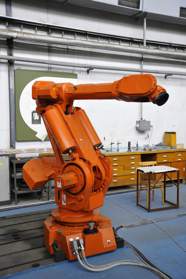 Robotic Arm. Orange robotic arm in factory hall royalty free stock images