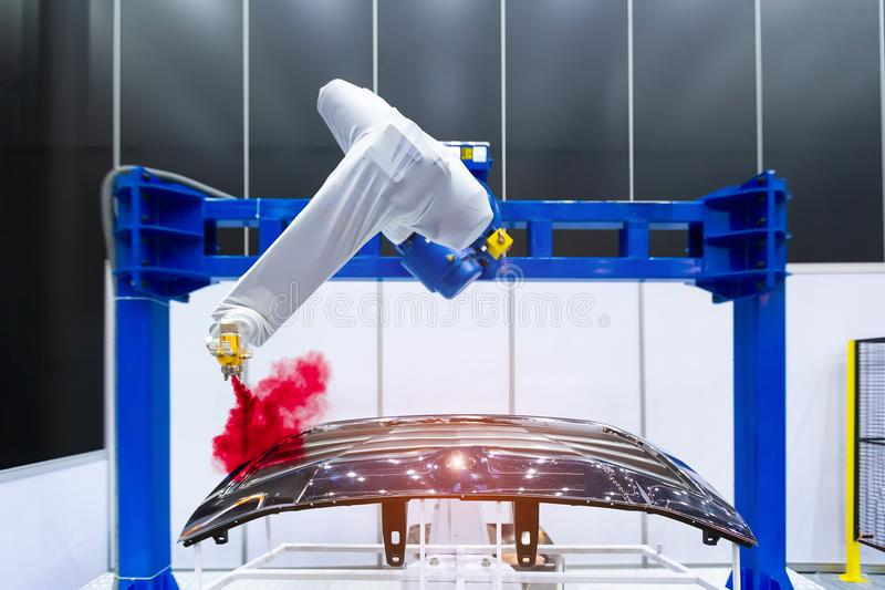 Robotic arm painting spray to the automotive part. High-technology manufacturing concept. royalty free stock image