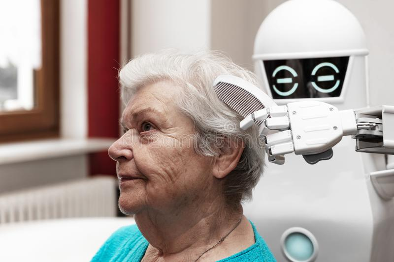 A robotic caregiver is combing the hair of a female senior adult royalty free stock photography