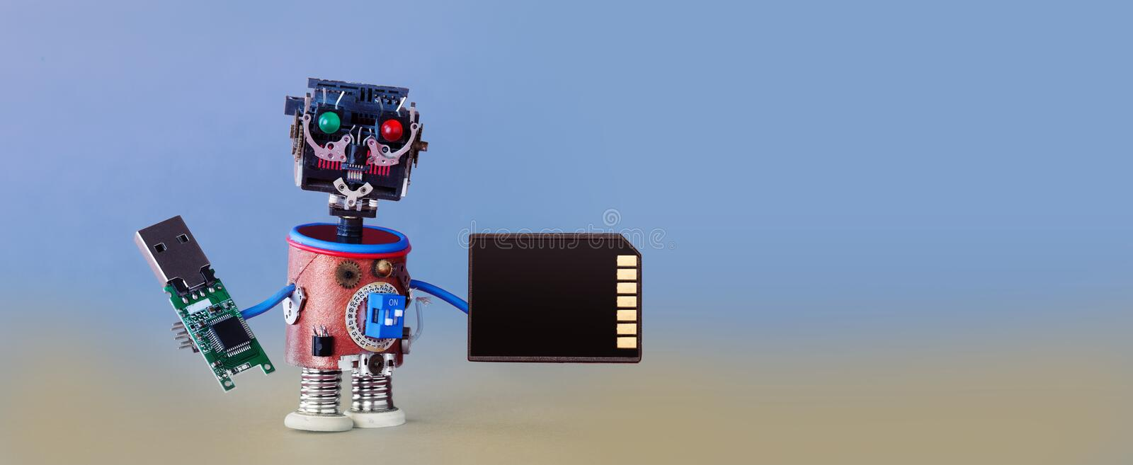 Robotic cyber safety data storage concept. System administrator cyborg toy with usb flash stick and memory card on blue. Gray gradient background. Copy space stock photos