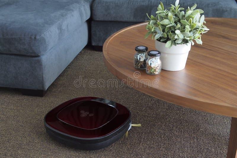 Robotic dammsugare på matta i vardagsrum arkivbild