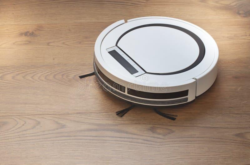 Robotic dammsugare på trägolvet Modern apparat för att göra ren arkivfoton