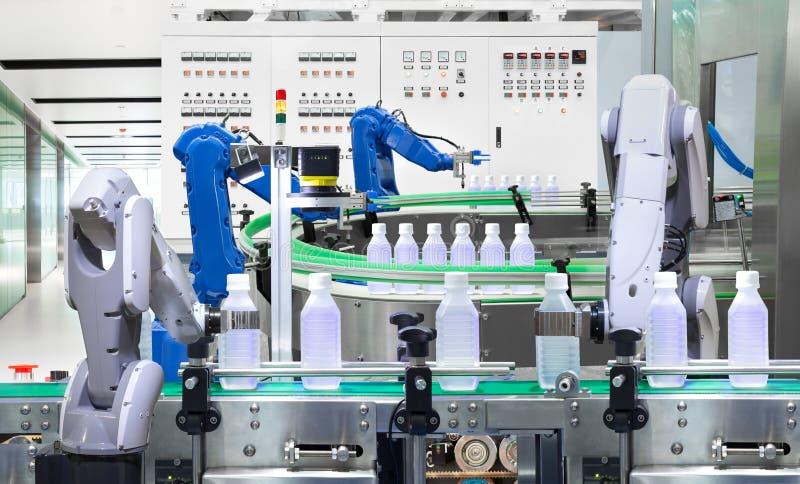 Robotic flaskor för vatten för arminnehav på produktionslinje i fabrik, arkivbilder