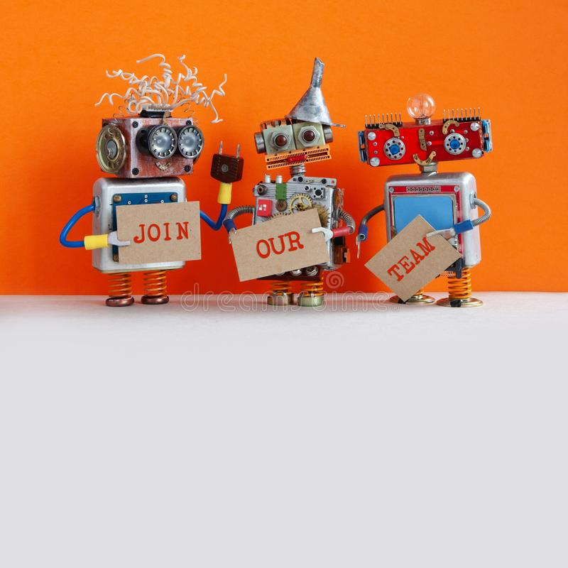 Robotic hiring recruitment concept. Three funny robots looking for a new assistant in company. Hr cyborgs holds a. Cardboard posters handwritten text Join Our royalty free stock images