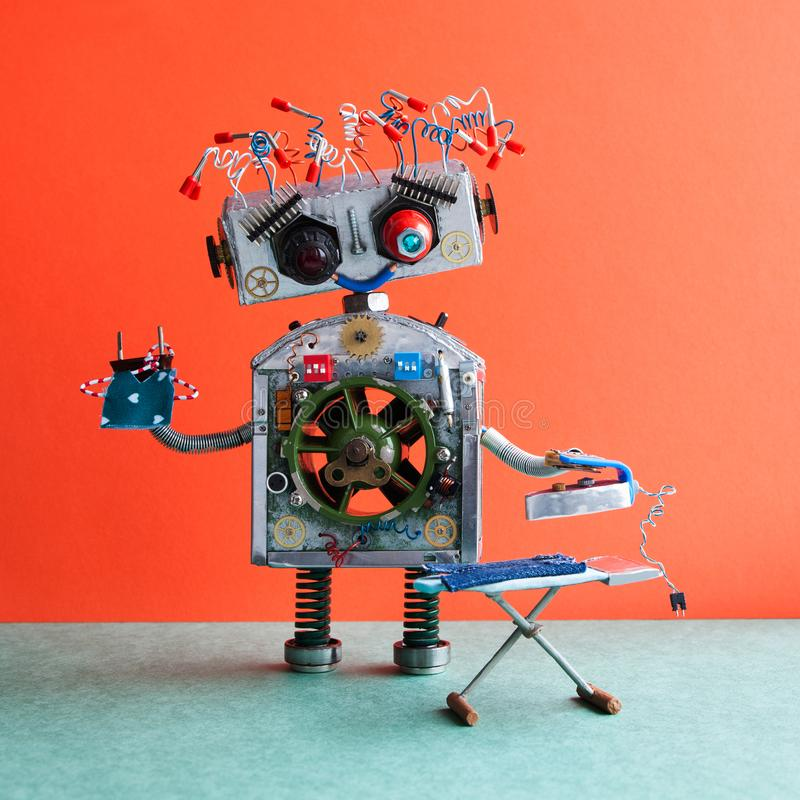 Robotic ironing service concept. Big robot housework assistant ironing blue jeans with iron on the board. Orange wall. Green floor royalty free stock photo