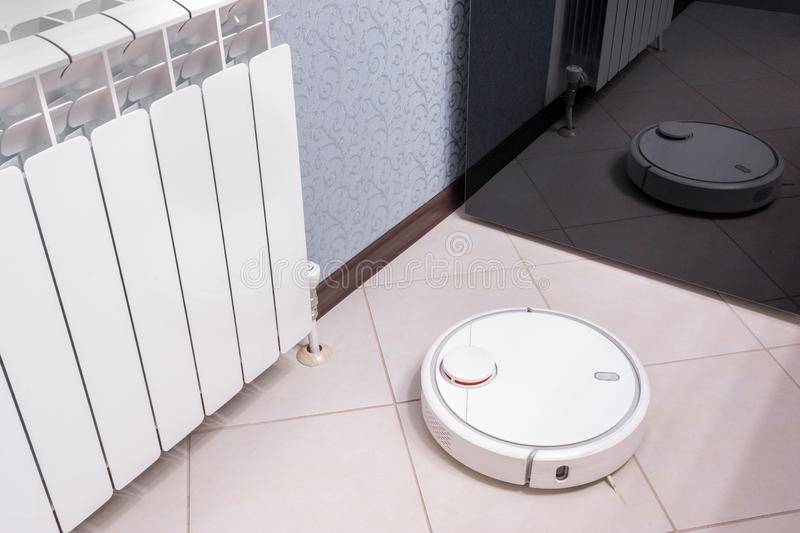 Robotic vacuum cleaner on laminate floor is reflected in mirror of fridge, smart home robotics wireless cleaning for simplify. Routine housework, efficient dust stock photography