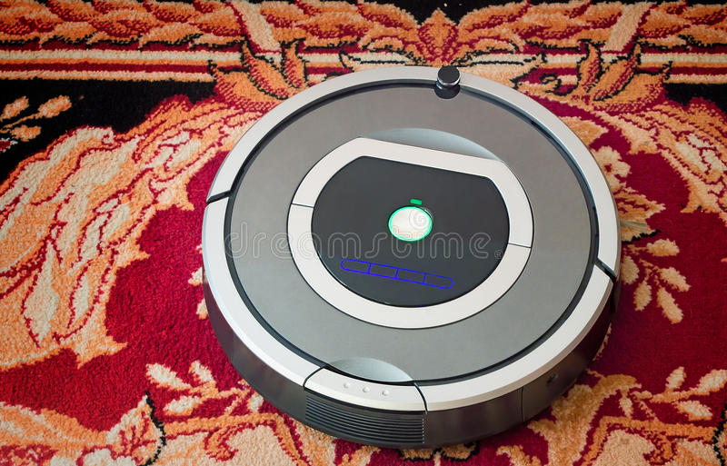 Robotics - the automated robot the vacuum cleaner. The automated robot vacuum cleaner of a roundish form, can make cleaning in hard-to-reach spots royalty free stock photos