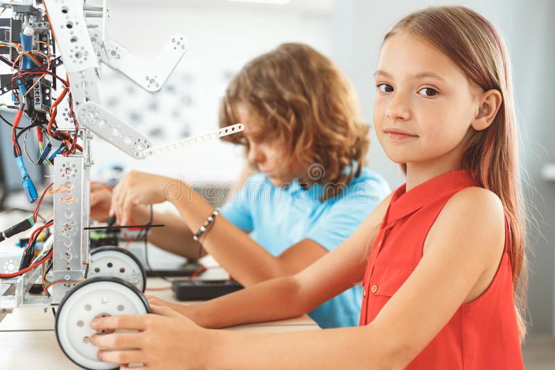 Robotics. Children sitting having class making robots girl close-up looking camera curious stock photo
