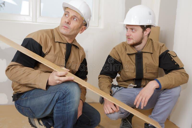 Robotniczy przysiadły patrzeje floorboard zdjęcie stock