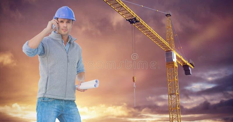 Robotnik dzwoni someone blisko do żurawia z purpurowym niebem obraz stock